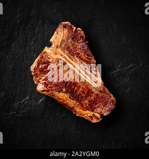 Flat lay of grilled T-bone steak on stone table - Stock Photo