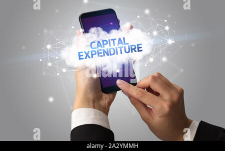Female hand touching smartphone with CAPITAL EXPENDITURE inscription, cloud business concept - Stock Photo