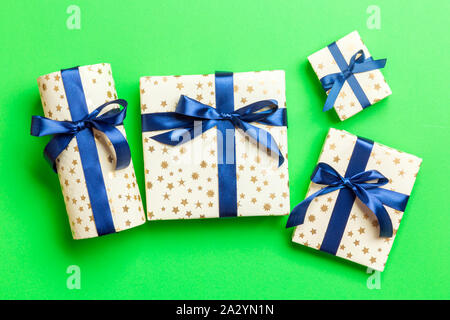 wrapped Christmas or other holiday handmade present in paper with blue ribbon on green background. Present box, decoration of gift on colored table, t - Stock Photo