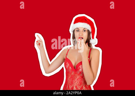 Young beautiful girl in christmas hat surprised pointing with fingers. Recommend advertising concept. Magazine collage style with trendy color backgro - Stock Photo