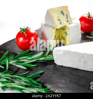 Assorted cheeses on wooden board. Camembert, cheese with blue mildew, mozzarella with tomatoes - Stock Photo