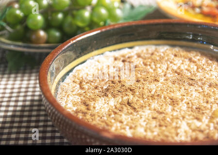 Typical Spanish arroz con leche, rice pudding on a table covered by a tablecloth served with some fruits and in a rustic kitchen. Empty copy space. - Stock Photo
