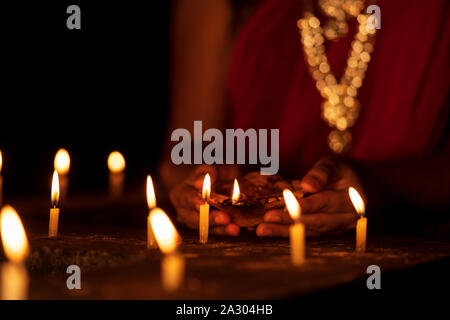 Happy Diwali. Indian newly wed bride wearing traditional saree with jewelery & illuminating candles with clay oil lamp or diya at Diwali night. Backgr - Stock Photo