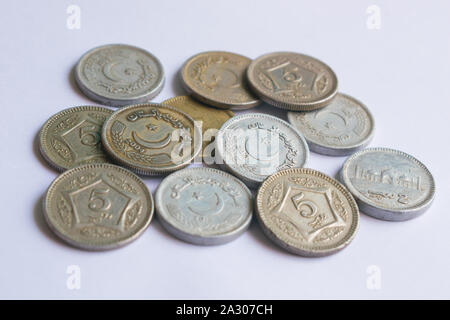 close up of pile of pakistani five rupee coins isolated on white background - Stock Photo