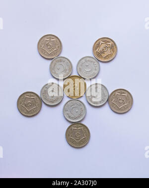 close up of pile of pakistani five rupee coins isolated on white background. - Stock Photo