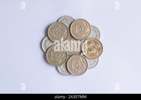 close up of pile of pakistani five rupee coins isolated on white background.coins in pantagone shape. - Stock Photo