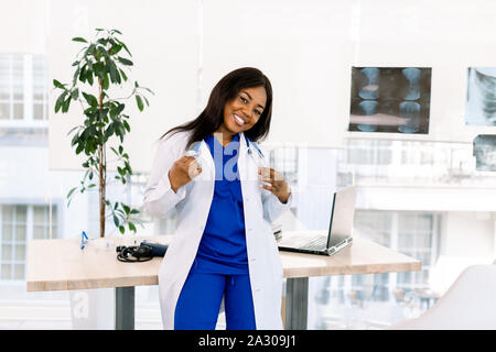Cute young African American doctor female with long hair wearing medical uniform having happy expression. Medical and nurse concept - Stock Photo