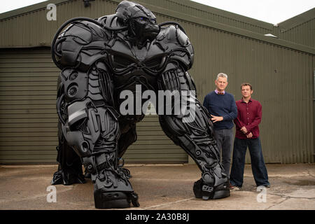Sculptor Luke Kite, with Chairman of the British Ironworks Centre Clive Knowles (left), stands by his 12ft sculpture of a gorilla, entitled 'Gorilla Apocalypse', created entirely from scrap car bumpers and panels discarded from only the last decade, on display at the British Ironwork Centre in Oswestry, Shropshire. - Stock Photo