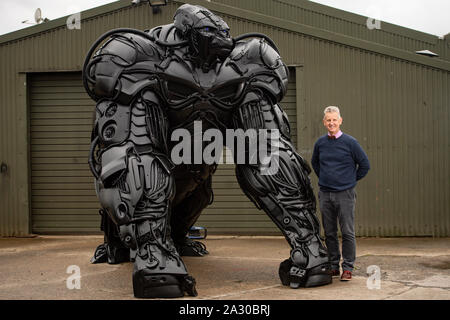 Chairman of the British Ironworks Centre Clive Knowles stands by Luke Kite's 12ft sculpture of a gorilla, entitled 'Gorilla Apocalypse', created entirely from scrap car bumpers and panels discarded from only the last decade, on display at the British Ironwork Centre in Oswestry, Shropshire. PA Photo. Picture date: Friday October 4, 2019. The sculpture, named 'Bumper Joe' during production, serves as a protest against the perceived negative effects the global car industry has on the planet. Photo credit should read: Jacob King/PA Wire - Stock Photo