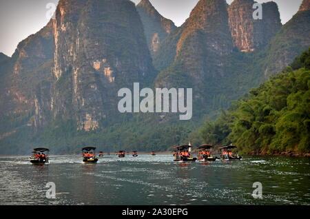Li river park tourist motor boats below dramatic mountain peaks, Guangxi, China - Stock Photo