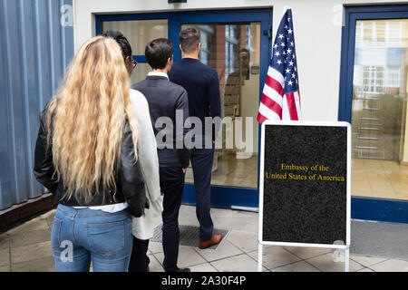 Group Of Young People Standing At The Entrance Of US Embassy - Stock Photo
