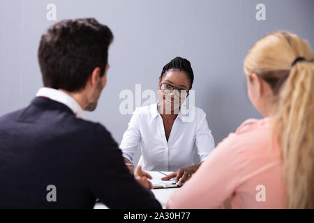 Couple Sitting And Talking At Interview At Adoption Agency - Stock Photo