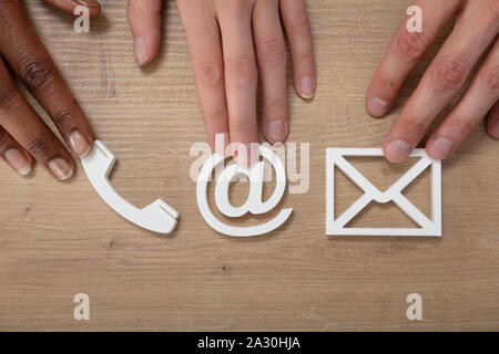 People Holding Email, Envelope, Phone, Icons On Wooden Desk - Stock Photo