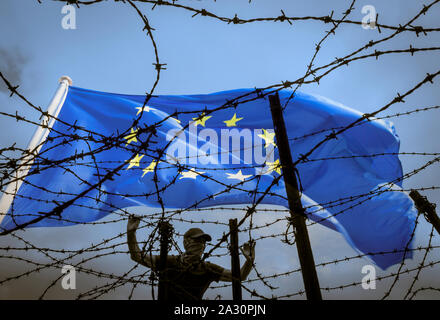 Brexit, immigration, asylum seekers... concept image. Man looking through barbed wire fence under EU flag. - Stock Photo