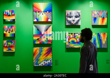 London, UK.  4 October 2019. A visitor views colourful works by Okuda San Miguel at Moniker International Art Fair, an urban contemporary art fair celebrating its 10 year anniversary in the UK.  The fair is on at Chelsea's Sorting Office until 6 October 2019.    Credit: Stephen Chung / Alamy Live News - Stock Photo