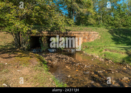 A clear water stream flowing with small waterfalls through an old rustic stone bridge surrounded by trees on a bright sunny day in early autumn - Stock Photo