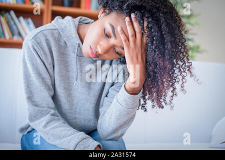 Sad woman lying on the couch at home feeling bad