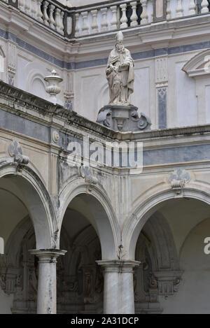 Carthusian Saint statue stands above marble columns in the Chiostro Grande, a former monastery complex, Certosa di San Martino, Naples, Italy, Europe. - Stock Photo