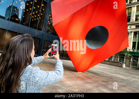 Young woman tourist photographs Isamu Noguchi's iconic Red Cube in Lower Manhattan, New York City, USA. - Stock Photo
