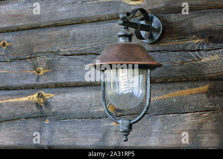 Horizontal shot of a street lamp hanging on the wall from old weathered and grayed logs on a Lithuanian farm. - Stock Photo
