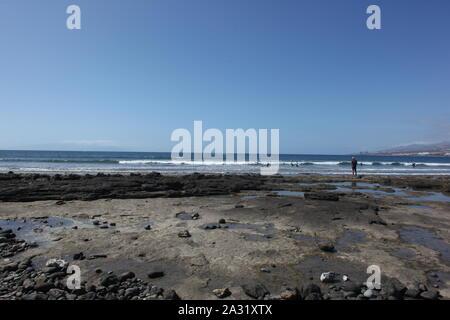 Surfers in the sea at Playas de las Americas, Tenerife, Canary Islands. - Stock Photo
