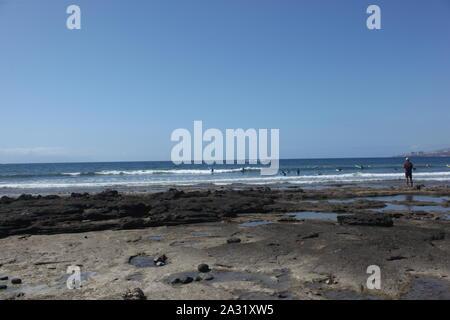 Surfers in the sea at Playa de las Americas, Tenerife, Canary Islands. - Stock Photo