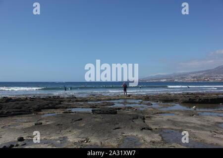 Surfers in the sea at Playa de las Americas, Tenerife. - Stock Photo