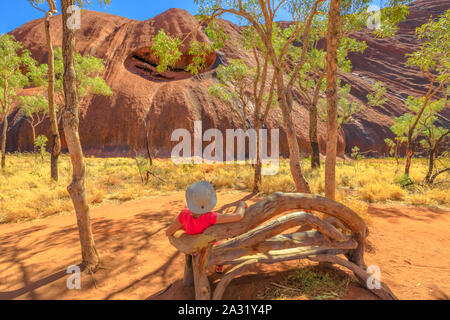 Tourist woman with wide hat rest on wooden bench along Uluru Base walk at southern face of Ayers Rock in Uluru-Kata Tjuta National Park. Tourism in - Stock Photo