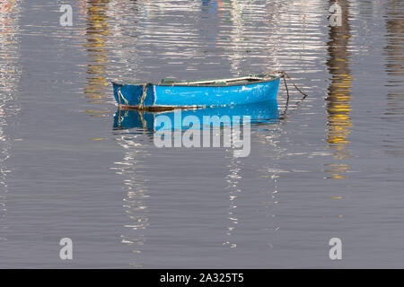 empty blue rowing boat with reflections