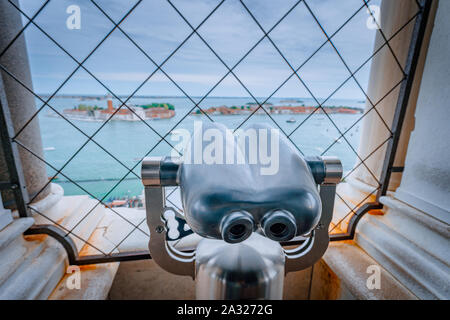 Binoculars in the Clock Tower of Venice, Italy with Chiesa di San Giorgio Maggiore blurred in background. Travel, vacation and tourism concept - Stock Photo