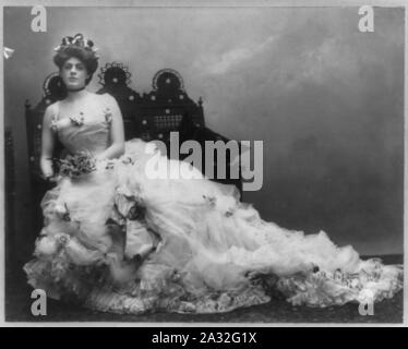 Ethel Barrymore, 1879-1959, full length portrait, seated, wearing long gown, bouquet in hands, facing slightly left - Stock Photo