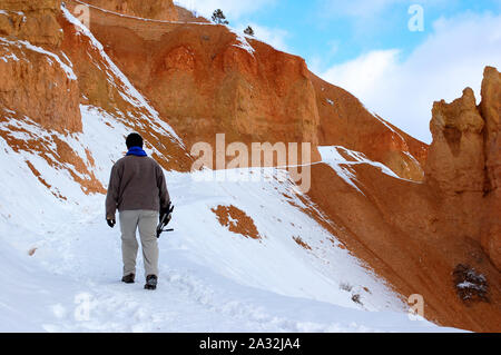 Young man hiking on snowy trail in red rocks mountain in bryce canyon - Stock Photo