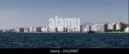 Cityscape of Thessaloniki city in Greece as seen from thermaikos, birds flying over White Tower, sunny day - Stock Photo