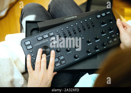 Paris, France - Spe 13, 2019: overhead view of female video editor vlogger retoucher woman holding unboxing new Loupedeck Plus photo and video editing console - Stock Photo