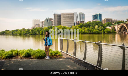 Teen standing by river in blue coat with office buildings in the background - Stock Photo