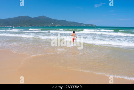 Da Nang Beach: an excited man runs through the surf to the gentle sea waves on My Khe Beach. Son Tra Peninsula and mountain on the horizon - Stock Photo