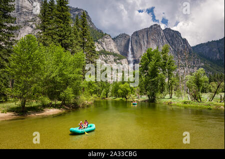 California, USA, 04 Jun 2013: Tourists enjoying ride on river with Yosemite Falls in background. - Stock Photo
