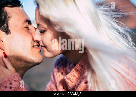 Romantic close up portrait of yong people kissing and enjoying love together - blonde caucasian girl and handsome boy with. closed eyes and close lips - Stock Photo