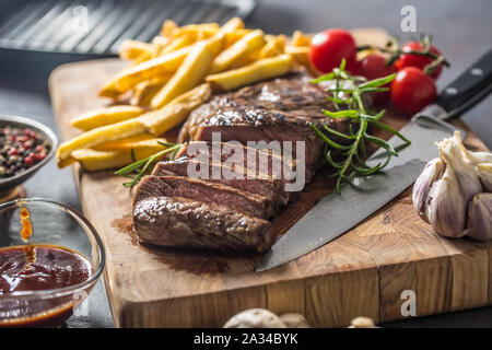 Beef Rib Eye steak with roasted potatoes bbq sauce garlic mushrooms and spices. - Stock Photo