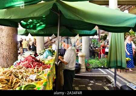Funchal, Madeira, Portugal - 16 August 2019: An old seller under a green umbrella in the fruit and vegetables market - Stock Photo