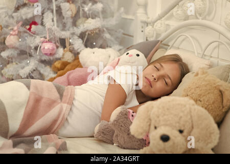 Enjoying xmas at home. Little child sleep at Christmas tree. Little girl lying in bed with toys. Cute girl fell asleep on Christmas night. Sleeping child. Peaceful sleep and rest on winter holidays. - Stock Photo