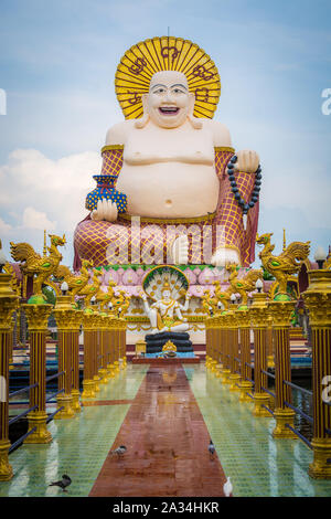 Giant smiling or happy buddha statue with blue sky in buddhist temple ( wat plai laem ), Koh Samui, Thailand. - Stock Photo