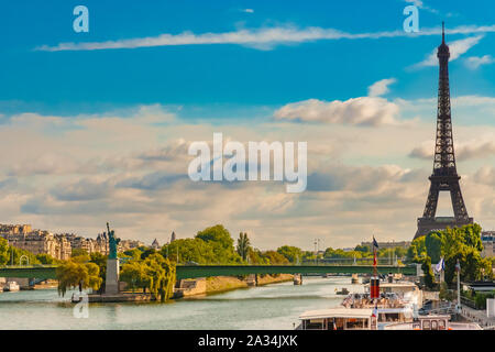 Lovely panoramic view of the Eiffel Tower together with the Statue of Liberty replica on the island Île aux Cygnes and the Pont de Grenelle bridge on - Stock Photo