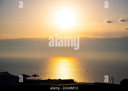 The sun setting behind clouds on the horizon of the Aegean sea seen from a clifftop restaurant in Oia - Stock Photo