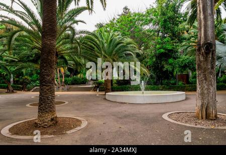 A small round fountain between floral clock and central fountain in Garcia Sanabria public park, Santa Cruz de Tenerife, Canary Islands, Spain - Stock Photo