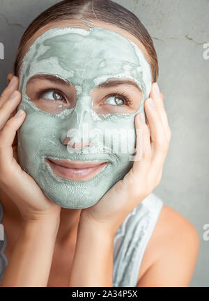 Portrait of a happy woman doing facial mask of a blue clay, at home, with pleasure touching face with her hands, pampering and beauty treatment - Stock Photo