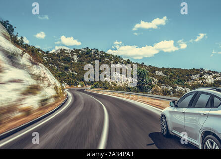 Car moves on the road among the mountains and forests. - Stock Photo