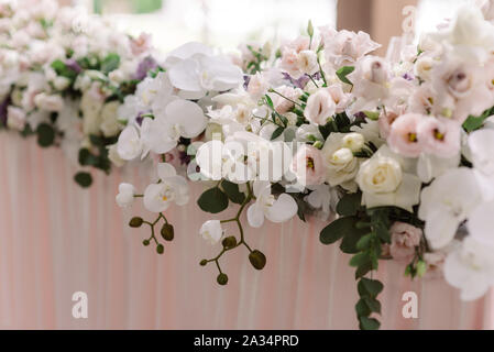 A long composition of fresh luxury flowers on the wedding table of the groom and bride. Decoration of the wedding with flowers in walled tones