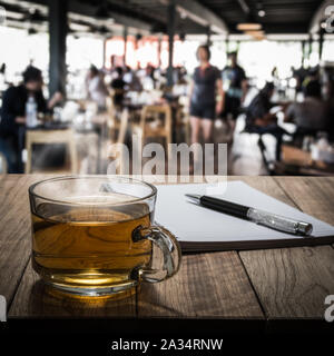 Hot tea with notebook and pen on wooden table in the coffee shop under light - Stock Photo