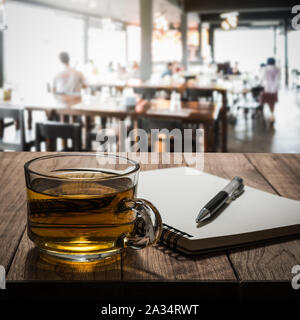 Hot tea with notebook and pen on wooden table in the coffee shop - Stock Photo